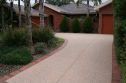 Light Aggregate concrete driveway with red brick edge